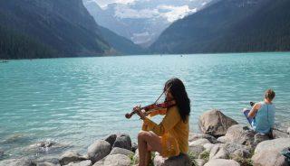 נגנית כינור על גדות אגם לואיז ברוקיס הקנדיים. צילום: בוריס פקלצ'יק