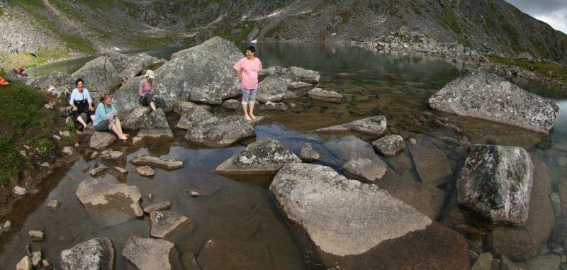 Hikers taking a break in Gold Cord Lake, Hatcher Pass, Alaska