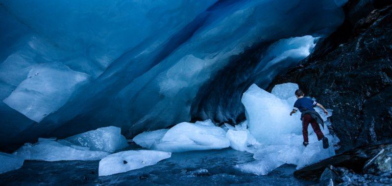 Kid walking on ice near an ice cave, Alaska