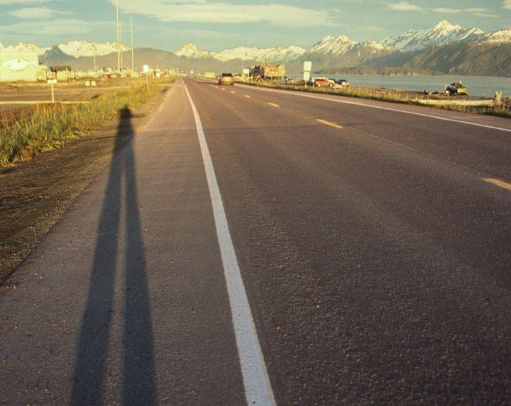 Long shadow of a hitchhiker, Homer Spit, Alaska